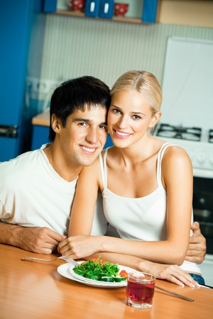 Young happy couple with salad at home together photo