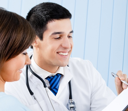Happy smiling doctor and young female patient with prescription at office photo