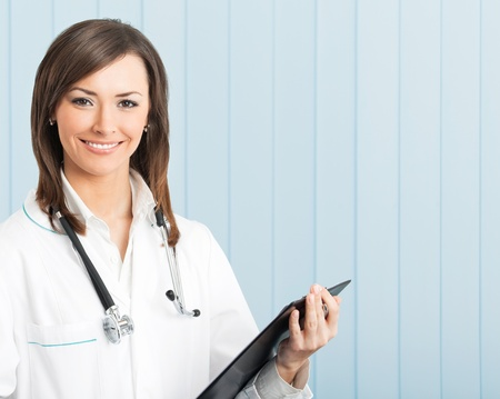 only one woman: Portrait of happy young smiling female doctor with clipboard at office