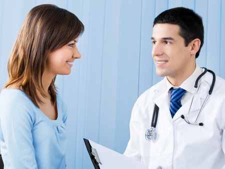 patient and doctor: Portrait of happy smiling female patient and doctor at office. Stock Photo