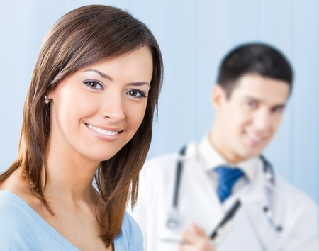 Portrait of happy smiling female patient and doctor at office. Focus on woman. photo