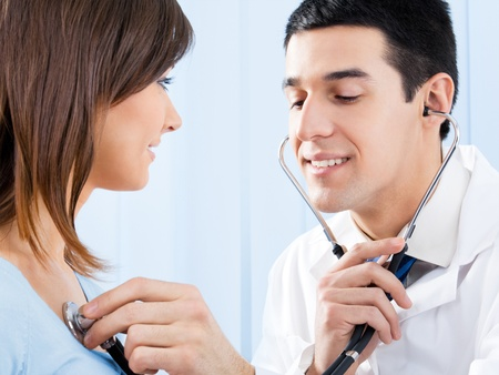 Happy smiling doctor with stethoscope and female patient at office Stock Photo - 12074579
