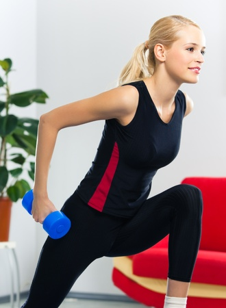 Portrait of young happy smiling woman in sportswear, doing fitness exercise with dumbbell, at home photo