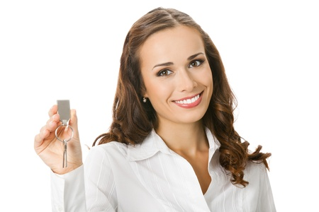 Young happy smiling business woman or real estate agent showing keys from new house, isolated over white background photo
