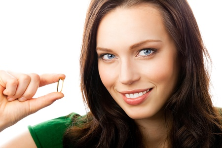 fish oil: Portrait of young happy smiling woman showing Omega 3 fish oil capsule, isolated over white background Stock Photo