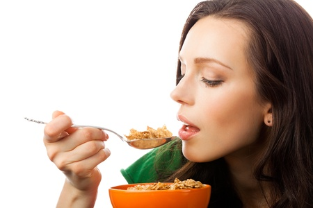 Portrait of young smiling woman eating muesli or corn flakes, isolated over white background photo