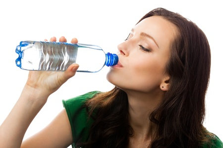 Young woman drinking water from bottle, isolated over white background photo