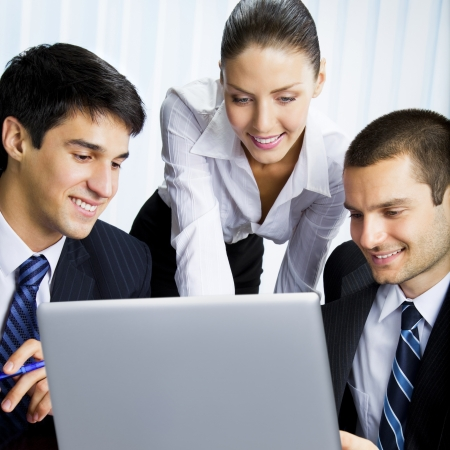 Three happy smiling successful business people working with laptop at office Stock Photo - 12234699