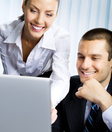 Two happy smiling cheerful business people working with laptop at office photo