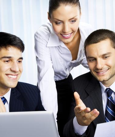 Tres empresarios que trabajan con el documento en la oficina photo