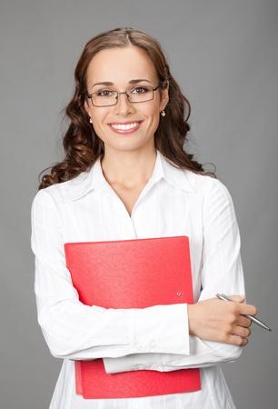 教師: 幸福的微笑業務女人用紅色的文件夾,在灰色背景的肖像 版權商用圖片
