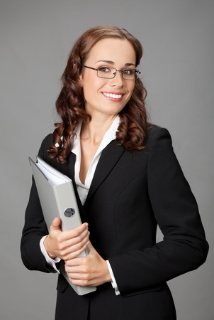 Portrait of happy smiling business woman with gray folder, over gray background photo