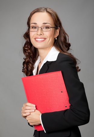 Portrait of happy smiling business woman with red folder, over gray background photo