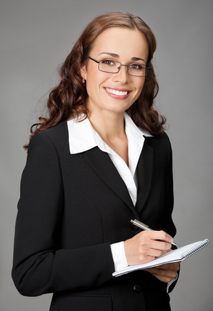 Portrait of happy smiling thinking business woman with notepad or organizer, over gray background photo