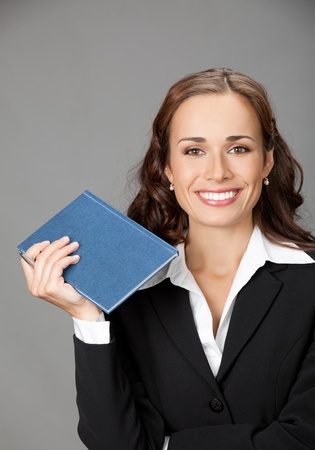 Portrait of happy smiling thinking business woman with blue notepad or organizer, over gray background Stock Photo - 12234684