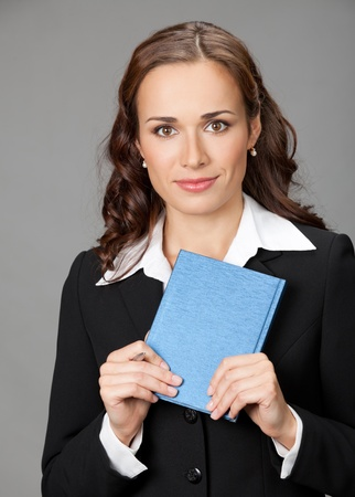 Portrait of happy smiling thinking business woman with blue notepad or organizer, over gray background Stock Photo - 12234695