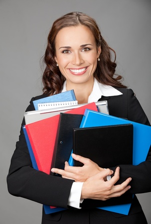 Portrait of happy smiling business woman with folders, over gray background photo
