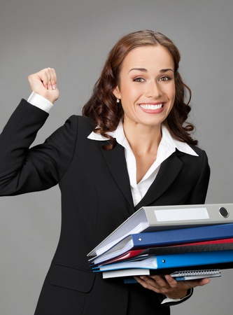 Portrait of happy gesturing smiling business woman with folders, over gray background photo