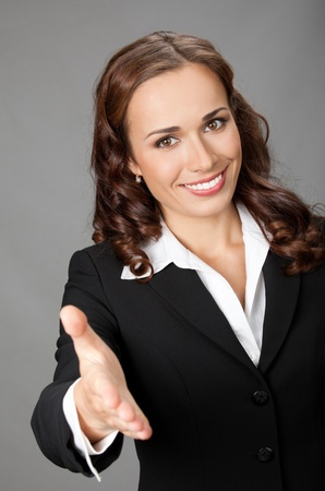 cheer: Portrait of young cheerful beautiful business woman giving hand for handshake, over grey background