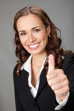 Happy smiling business woman showing thumbs up gesture, over grey background Stock Photo - 12234680