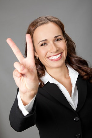 Happy smiling beautiful young business woman showing two fingers or victory gesture, over gray background Stock Photo - 12234673