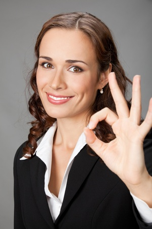 Happy smiling cheerful young business woman with okay gesture, over grey background Stock Photo - 12234681