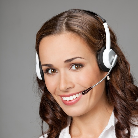 Portrait of happy smiling cheerful customer support phone operator in headset, over gray background Stock Photo - 12234693