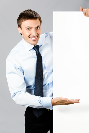 Happy smiling young business man showing blank signboard, over gray background photo