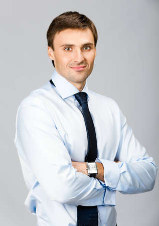 Portrait of young happy smiling business man, isolated over grey background