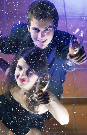 Young happy couple at celebration with glasses of champagne photo
