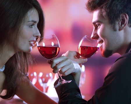 date night: Young happy amorous couple with glasses of redwine on romantic date at restaurant