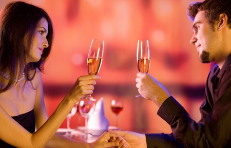 Young happy amorous couple with glasses of champagne on romantic date at restaurant photo