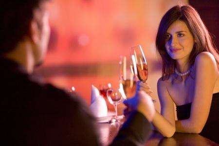 coquetear: Joven pareja feliz amorosa con copas de champ�n en la cita rom�ntica en el restaurante