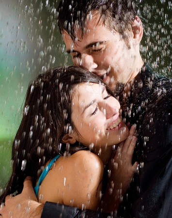 Young happy amorous couple hugging under a rain, outdoors Stock Photo - 12910758
