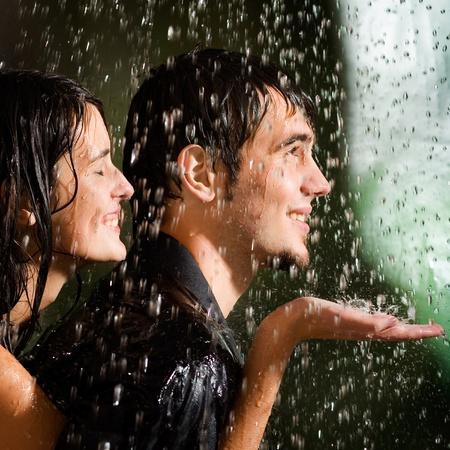 lloviendo: Joven pareja feliz amorosa bajo una lluvia, al aire libre Foto de archivo