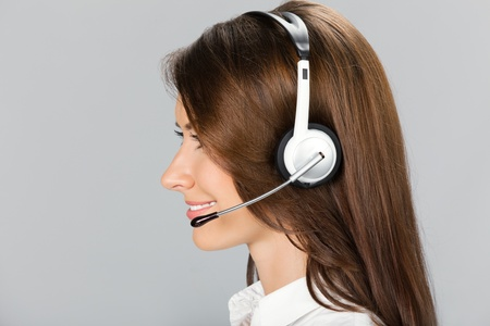 Portrait of happy smiling cheerful customer support phone operator in headset, over gray background Stock Photo - 12926652