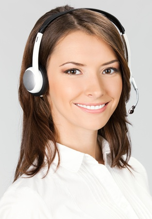 Portrait of happy smiling cheerful customer support phone operator in headset, over gray background Stock Photo - 12926647