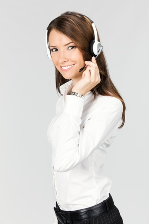Portrait of happy smiling cheerful customer support phone operator in headset, over gray background photo