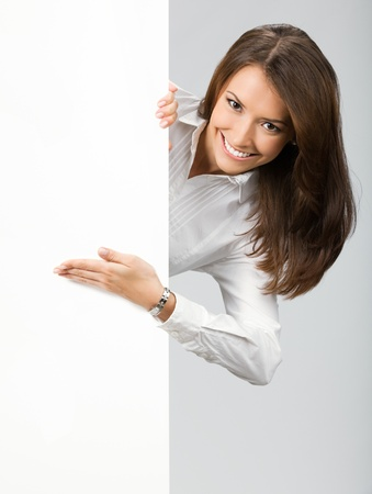 Happy smiling young business woman showing blank signboard, over grey background Stock Photo - 12910777