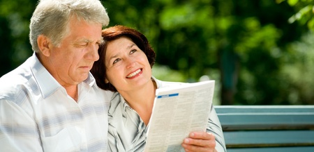 magazine reading: Happy smiling attractive senior couple reading together, outdoors, with copyspace