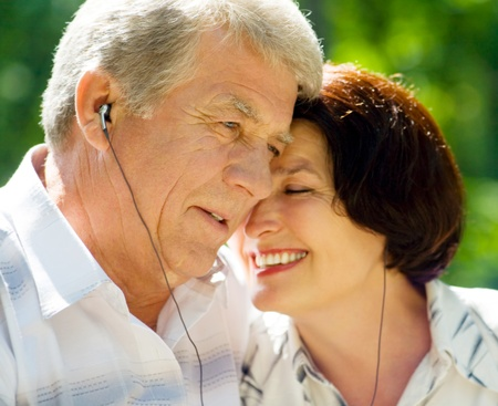Happy smiling cheerful senior couple listening music or audio book in headset or praying together, outdoors Stock Photo - 12926679