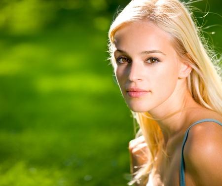 Porträt der lächelnden jungen schönen blonden Frau im Freien, mit copyspace
