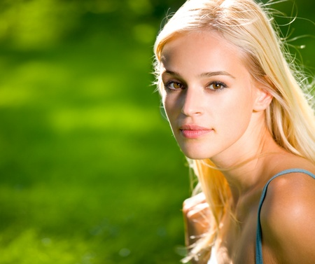 Portrait of smiling young beautiful blond woman outdoors, with copyspace Stock Photo