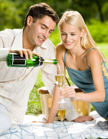 Happy smiling cheerful attractive young couple with champagne at picnic, outdoor photo