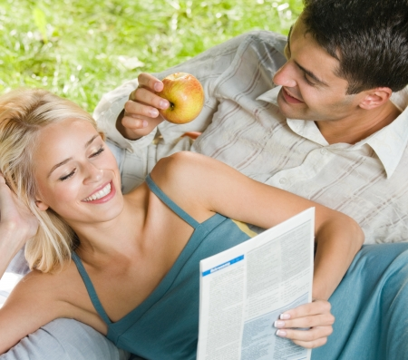 Young happy smiling cheerful couple reading together newspaper, outdoors