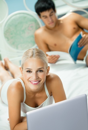 Young happy smiling couple working with laptop at bedroom photo