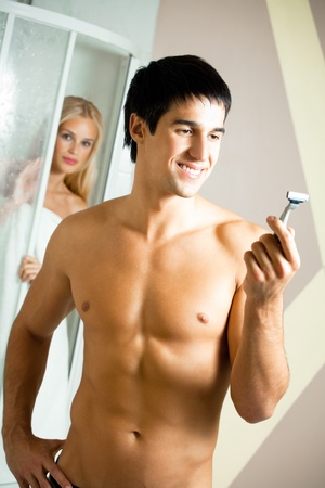 Shaving man and young woman at bathroom photo