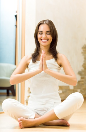 haciendo ejercicio: Joven mujer feliz haciendo ejercicios de yoga en casa