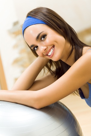 Young happy woman doing fitness exercises with fit ball at home Stock Photo - 12996405