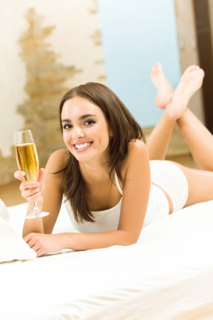 Portrait of young woman with glass of champagne, on bed photo
